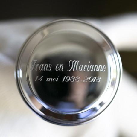 Gravering van twee namen met de trouwdatum eronder gecentreerd op een zilveren kurk
