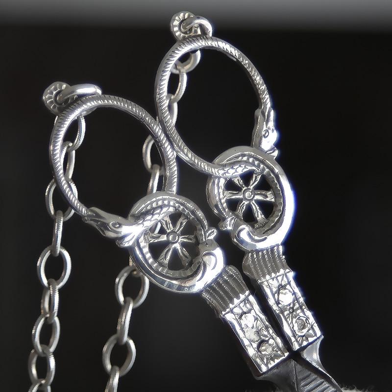 Antieke zilveren naaischaar de ogen in de vorm van een slang die zijn staart opeet, de Ouroboros.