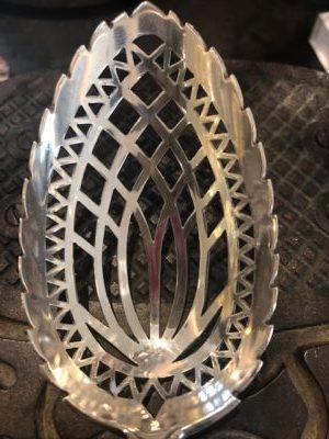 Met de hand uitgezaagd patroon in een zilveren natfruitlepel.