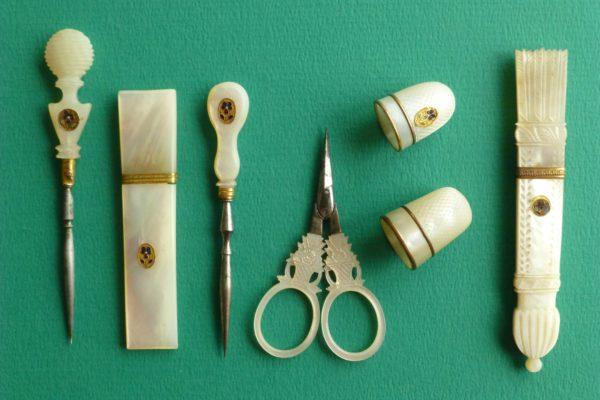 Naaigerei van parelmoer met goud en een viooltje
